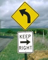 "Sign reads: ""keep right"" but has an arrow pointing to the left."