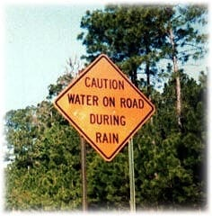 "Sign reads: ""water on the road during rain"""