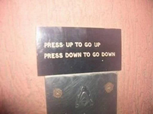 "Elevator sign reads, ""Press up to go up. Press down to go down."""