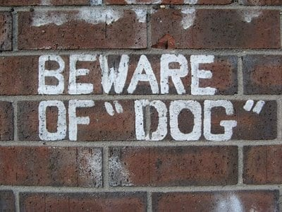 A brick wall with the words beware of dog painted on